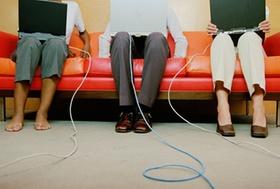 Personen auf Sofa mit Laptops