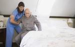 Pflegeperson die älterem Herr beim Aufstehen aus dem Bett hilft