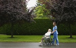 Pflegeperson die mit älterer Frau im Rollstuhl spazieren geht