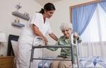 Pflegeperson hilft älterer Frau mit Gehhilfe vom Bett aufzustehen