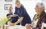 Pflegeperson schenkt altem Mann und alter Frau Kaffee ein