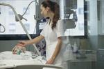 Pflegerin streicht älterer Frau in einem Krankenbett über den Kopf