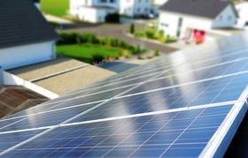 Photovoltaik-Anlage auf Dach mit Häusern im Hintergrund