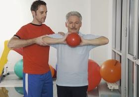 Reha-Klinik, aelterer Mann mit Therapeut bei Uebung mit Ball