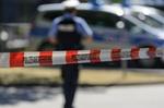Polizeiabsperrung mit Flatterband, hinten Streifenwagen und Polizeibeamter