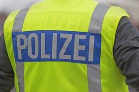 Polizeibeamter mit Warnweste, Aufschrift Polizei, Rückenansicht