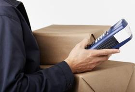 Postbote schaut auf Scanner und Paket