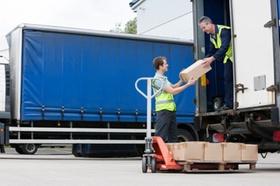 Postbote übergibt Pakete aus LKW