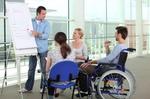 Präsentation an Flipchart vor Leuten von denen einer im Rollstuhl sitzt