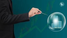 Immobilien-Preisblase Mann im Anzug sticht mit einer Nadel in eine Blase mit einer Immobilie