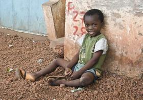 Afrikanisches Kind sitzt auf Boden