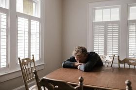 Psychische Belastung: Mann legt Kopf auf dem Tisch