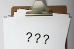 Reißbrett mit drei Fragezeichen
