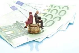 Rentnerpaar-Figuren sitzen auf Stapel aus Münzen und Scheinen