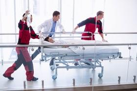 Rettungssanitäter und Arzt rennen mit Patient in Notaufnahme