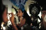 Revue-Dame mit blauem Federschmuck sitzt in der Garderobe am Schminktisch