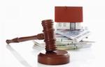 Richterhammer liegt vor Hausmodell auf Geldstapel