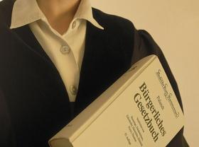 Buergerliches Gesetzbuch im Arm einer Richterin