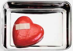 Rotes Herz mit Pflaster liegt in Metallschale