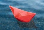 Rotes Papierschiffchen schwimmt auf Wasser