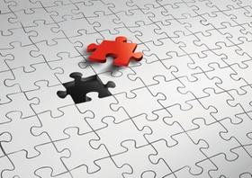Rotes Puzzleteil schwebt ueber Puzzle