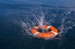 Round life preserver splashing into water