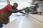 Schreiner Handwerker afrikanischer Abstammung sägt etwas zu