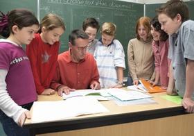 Schueler am Lehrertisch im Klassenzimmer