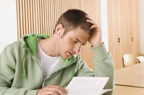 Schueler hoert mit Ohrhoerern Musik und liest ein Buch
