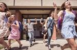 Teenage high school girls and boys running from school