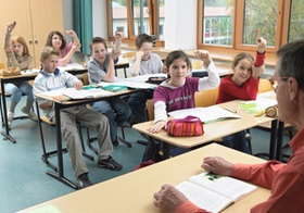 Schueler und Lehrer in Klassenzimmer, einige melden sich