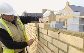Schutzhelm und Warnweste tragender Mann baut Mauer