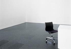 Schwarzer Stuhl an Tisch in leerem Raum