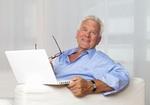 Senior sitzt mit Laptop auf Sofa