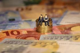 Senioren sitzen auf Geldmünzen