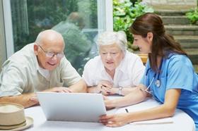 Senioren und Krankenschwester am Laptop Pflege planen