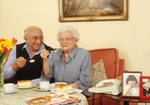 Älteres Seniorenpaar, sitzen zuhause bei Kaffee und Kuchen