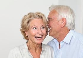 Seniorenpaar, er fluestert ihr etwas ins Ohr, Portraet