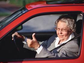 Seniorin am Steuer eines Autos, Gestik Daumen hoch