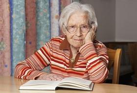 Seniorin liest ein Buch und schaut in die Kamera