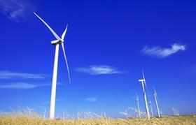 Sicht von unten auf Windräder vor blauem Himmel