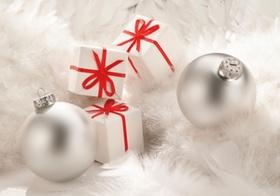 Silberne Christbaumkugeln, weisse Paeckchen mit roten Schleifen, Federn