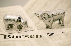 Silberner Bär und Bulle auf Börsenzeitungen
