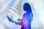 Silhouette einer Frau mit Laptop vor Hochhaus