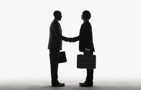 Silhouette zweier Geschäftsmänner beim Hände schütteln