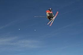 Skifahrer_Ski-Akrobat vor blauem Himmel in der Luft