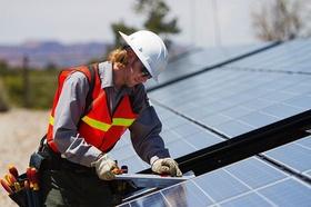 Solaranlage_ Arbeiter baut Solarzellen auf Dach