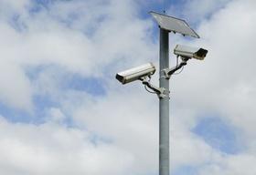 A solar powered surveillance camera on a pole.