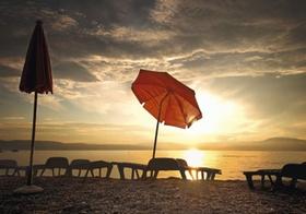 Sonnenschirm und Liegestuehle an Strand bei Sonnenuntergang
