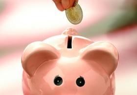 Sparschwein mit Geldmünze und Hand